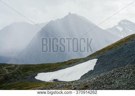 Wonderful Alpine Landscape With Giant Mountain With Pointed Pinnacle In Sunlight Through Clouds. Awe