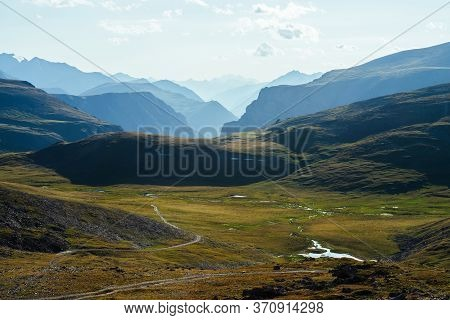 Great Rocky Mountains And Deep Gorge Behind Beautiful Green Valley With Lake In Highlands. Awesome M