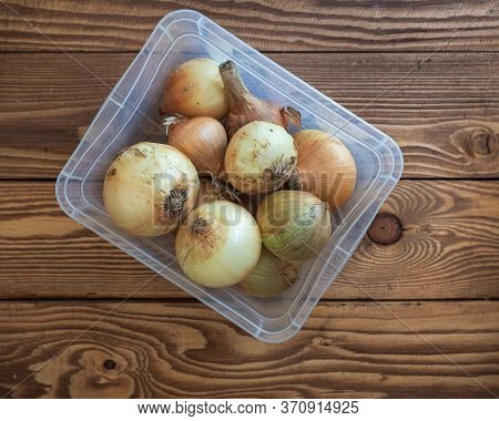Close-up Of A Container With Unpeeled Onions On A Wooden Table