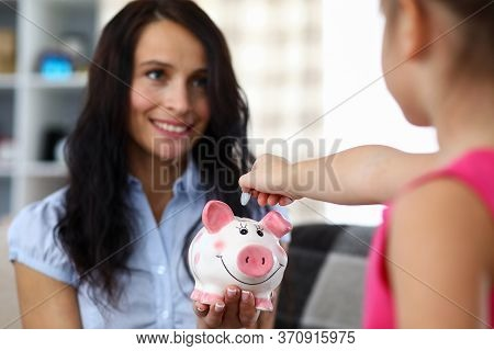 Portrait Of Happy Mother Holding Pink Funny Piggy Bank. Little Child Putting Money Into Thrift-box.