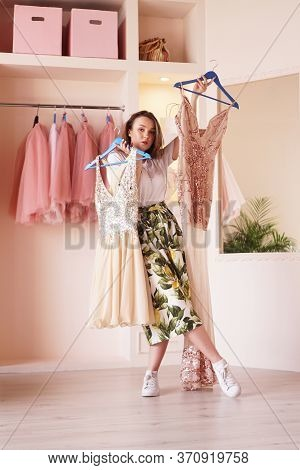 Young Woman Standing Near Wardrobe, Holding Dress On Hangers, Trying To Decide What To Wear. Pretty