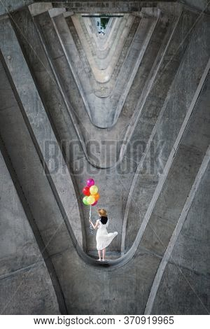 Portrait Of Woman Holding Colorful Balloons At Structure Of Cement Concrete Beams Under The Expressw