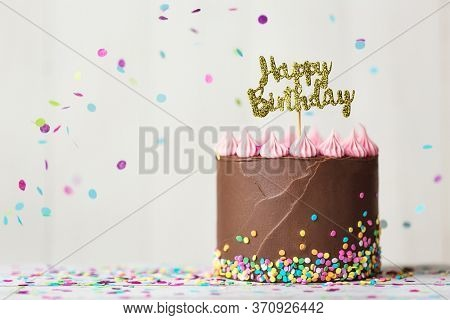Chocolate birthday cake with happy birthday banner and falling confetti