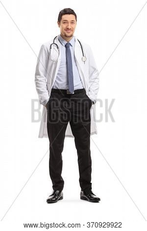 Full length portrait of a young male doctor smiling and posing isolated on white background