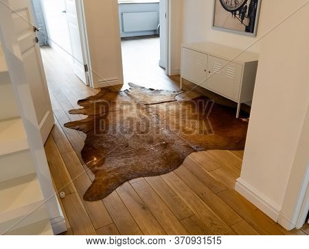 Reddish Brown Cowhide Rug With Silky Coat On A Wooden Floor As Luxuriously Home Decoration With Rust