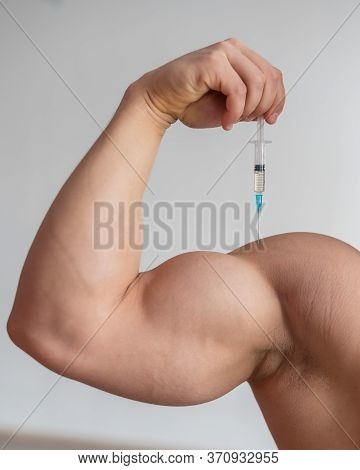 Closeup Of A Male Hand With A Dope Syringe. Cropped Biceps Of A Man. Unrecognizable Bodybuilder Sets