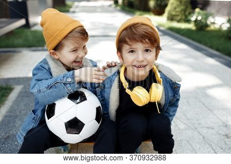 Two Cute Twin Boys With Happy Faces Sitting On The Skateboard Or Pennyboard In The Street.