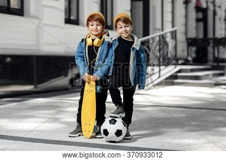 Two Funny Twin Boys Posing With Happy Faces In The Street. Skateboard Or Pennyboard And Soccer Ball.