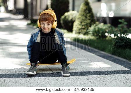 Photo Of Positive Little Boy Sitting On The Skateboard Or Pennyboard Listening Music In Headphones I