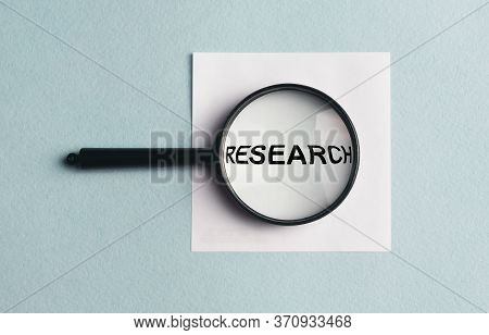 Research Concept, Word Research In Magnifying Glass Loupe On White Sticker Note On Blue Table. Medic