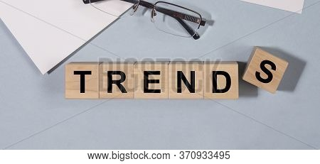 Word Trends On Cube Blocks On A Blue Grey Table With Glasses And Planner. Business Trends Or Office