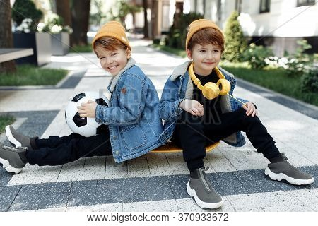 Two Stylish Twin Boys Sitting On The Skateboard Or Pennyboard Looking Each Over Up In The Street.