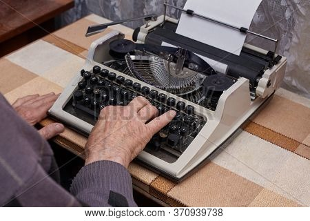 A Pensioner Is Typing On A Typewriter. The Typewriter Is Old. Horizontal Frame.