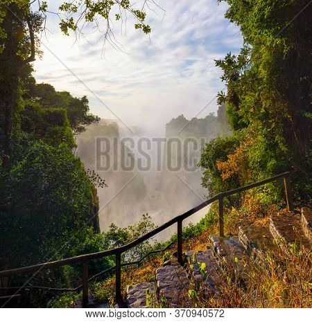 Staircase Going To The Victoria Falls On Zambezi River Located Between Zambia And Zimbabwe, The Larg