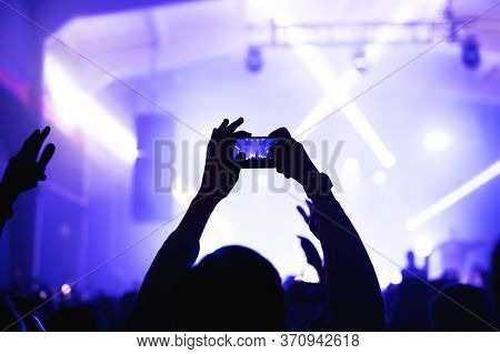 Atmosphere Of A Cool Music Festival With A Stage Floodlit With Hands From The Crowd With A Smartphon
