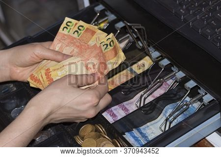 Saleswoman Hands At Cash Register With Brazilian Money Notes And Coins Inside The Electronic Cash Re