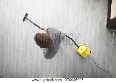 Top View Of Adult Male Cleaning In Room With Compact Yellow Vacuum Cleaner. Grey Laminate Floor In M