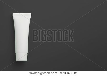 White Cosmetical Tube On Black Background. Health Care Mockup Concept