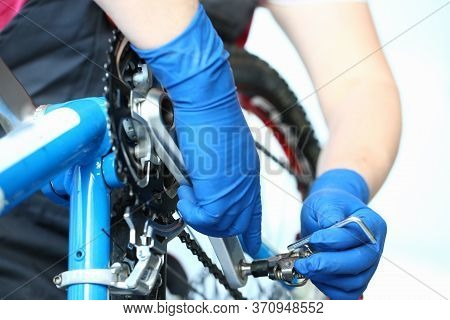 Close-up Of Mechanic Service Man Installing Assembling Or Adjusting Bicycle Gear On Wheel In Worksho