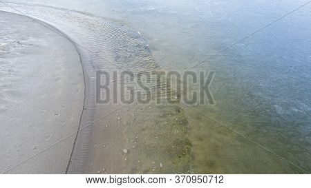 Coastline, Melting Ice, Clear Water On The Sandy Beach.