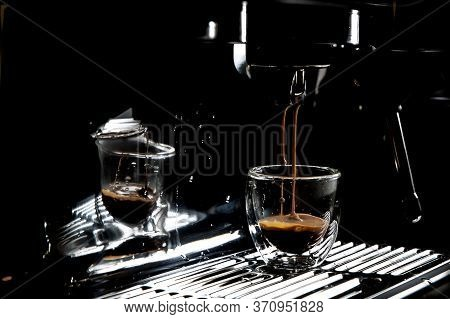 Dark Coffee Drops Dripping In A Transparent Glass Espresso Cup On A Manual Espresso Machine With Cop