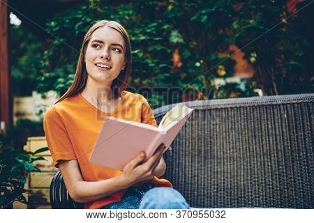 Smiling Thoughtful Young Woman With Book In Hands Pondering On Continuation Of Novel