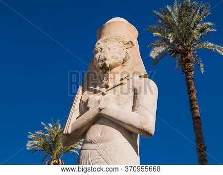 Luxor, Egypt - Jan 28, 2020: Mighty stone statue of Luxor Temple in Luxor, ancient Thebes, Egypt. Luxor Temple is a large Ancient Egyptian temple complex located on the east bank of the Nile River