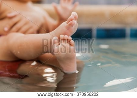 Baby Relaxing In A Hot Tub In The Backyard During Quarantine Time, Closeup Of Infant Feet In Water,