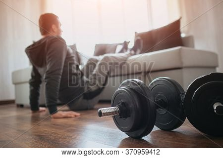 Young Ordinary Man Go In For Sport At Home. Hardworking Beginner Sit On Floor And Hold Legs On Sofa.