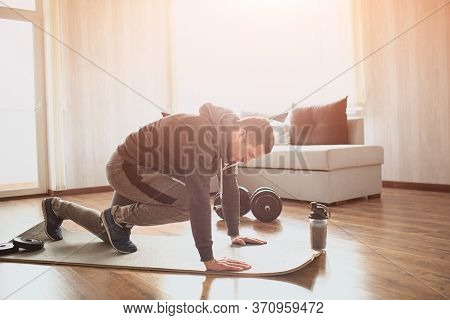 Young Ordinary Man Go In For Sport At Home. Picture Of Real Ordinary Man Doing Abs Exercising By Run