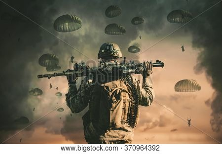 One Soldier Watching Soldiers In The Air With Parachute .