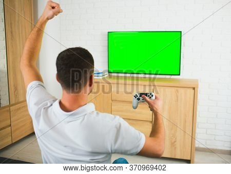 Young Man Sit In Room During Quarantine. Guy Playing Computer Games Using Joystick And Tv. Green Scr