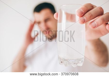 Young Sick Man Isolated Over Background. Guy Hold Glass Of Water With Effervescent Pills And Medicin