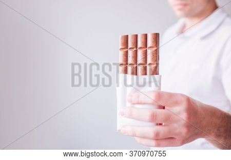 Young Man In White Shirt Isolated Over Background. Guy Hold Tasty Sweet Chocolate Bar In Hand And Po