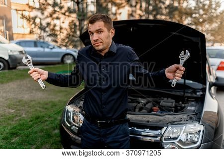 Car Breakdown Concept. The Car Will Not Start. The Young Man Tries To Fix Everything Himself, But He