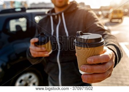 Disposable Paper Cup With Hot Drink. A Man Drinks Coffee Or Tea And Offers To Share A Drink With You