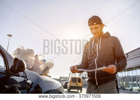 A Man Reads An Advertising Booklet In The Parking Lot Of A Shopping Mall. She Bought A Lot Of Food A