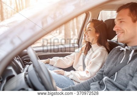 Happy Young Family Rides In A Car In The Forest. A Man Is Driving A Car, And His Wife Is Sitting Nea
