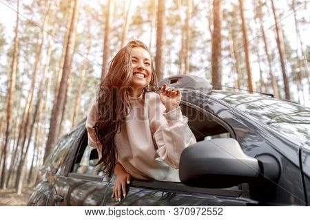 Happy Young Woman Climbed Out Of A Car Window. Traveling By Car In The Forest. Country Trip. Vacatio