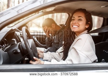 Driving Instruction. A Young Woman Learns To Drive A Car . Her Instructor Or Boyfriend Doesnt Like T