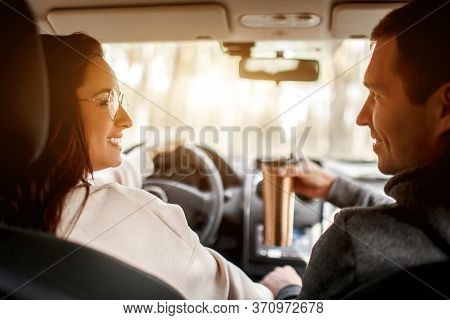 Happy Young Family Rides In A Car In The Forest. A Woman Is Driving A Car, And Man Is Sitting Nearby