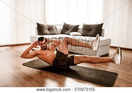 Young Man Go In For Sport At Home. Picture Of T-shirtless Guy Sportsman Doing Abs Exercising On A Yo