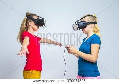 Virtual Reality Simulation. Pair Of Caucasian Twin Teenager Girls Playing With Vr (virtual Reality)