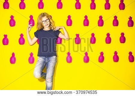 Teenager Concepts. Portrait Of Positive Teenage Girl Standing Against Yellow Wall With Lots Of Artif