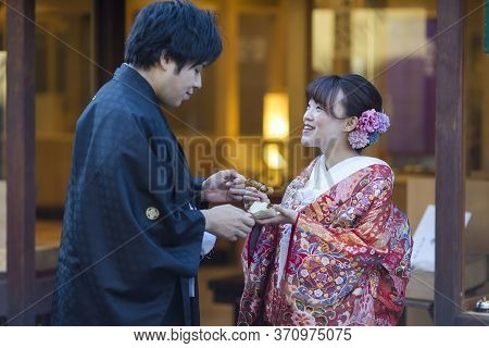 Kyoto, Japan - November, 8, 2019: Young Lovely Couple In Traditional Geisha Kimono Posing With Dango