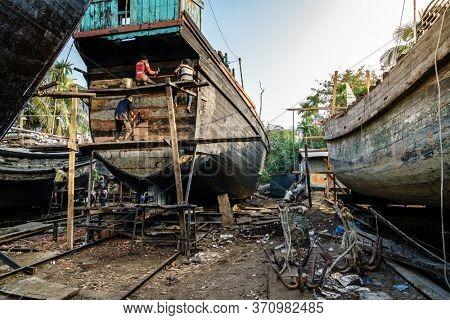 Chittagong, Bangladesh, December 22, 2017: Traditional fishing boats are being built at a shipyard by the Karnaphuli River near Chittagong, Bangladesh