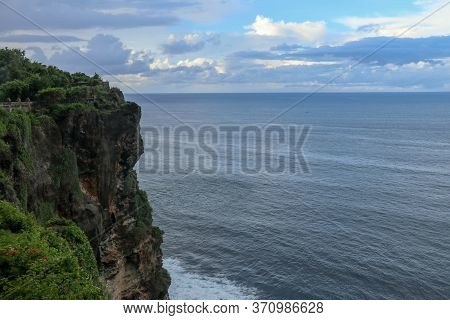 Overview Panorama Ocean Shore, Cliff. Sunset. Bali. Overwhelmed Scene The Flower And Green-capped Ve