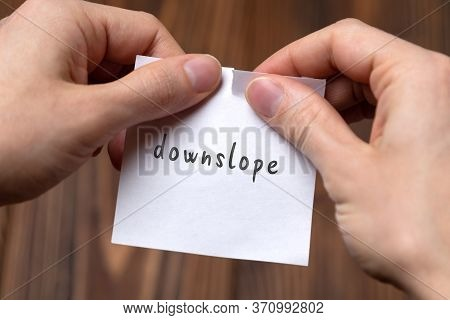 Concept Of Cancelling. Hands Closeup Tearing A Sheet Of Paper With Inscription Downslope
