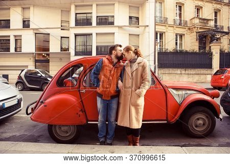 A Couple Man And Woman Stand At A Red Retro Car, Walking In Spring Paris. A Romantic Trip Together.