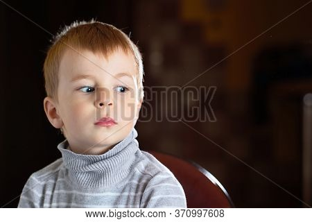 Facial Portrait Of Scared Pensive Blond Boy Looking Away With Fear Over Dark Background With Specks